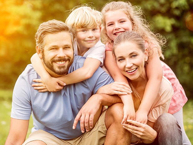 Smiling family of four outdoors
