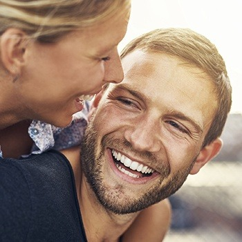 Young man and woman smiling together outdoors