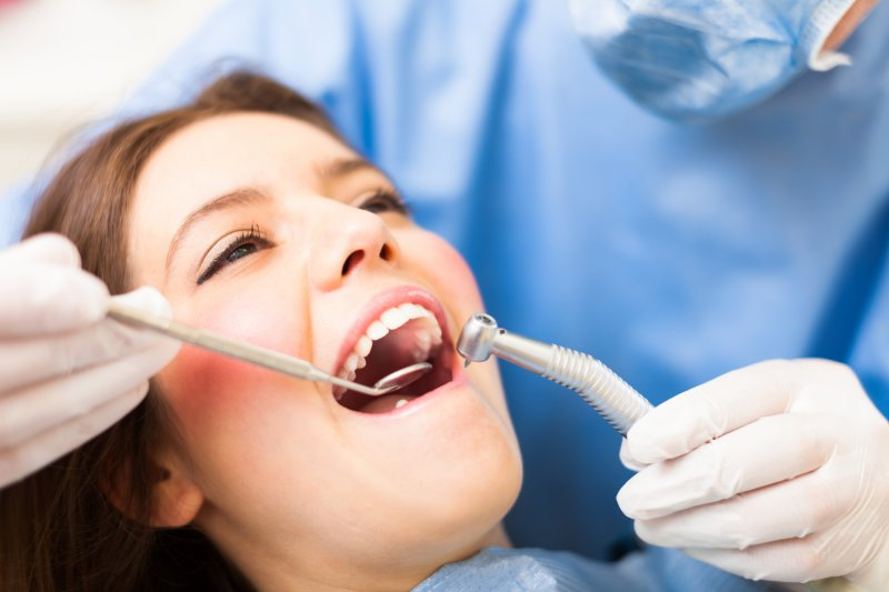woman dental chair undergoing oral examination