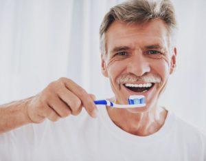 older man brushing his teeth