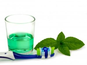 Toothbrush, mouthwash, and mint leaves
