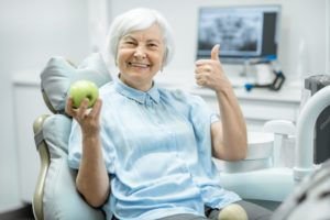 Woman holding an apple gives a thumbs up after visiting implant dentist