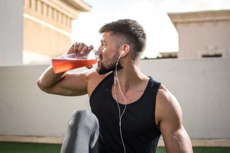 Man drinking a sports drink while exercising